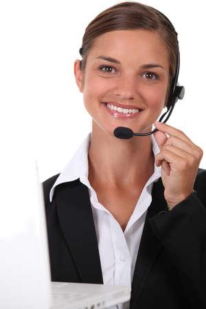 discreto: Recepcionista con auriculares y un ordenador