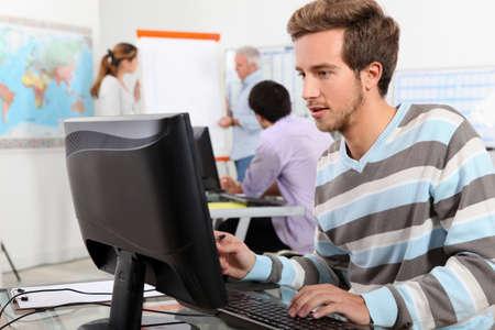 estudiantes adultos: Hombre joven que trabaja en un ordenador