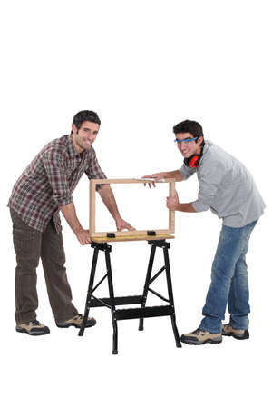 bent over: Tradesmen building a wooden frame Stock Photo