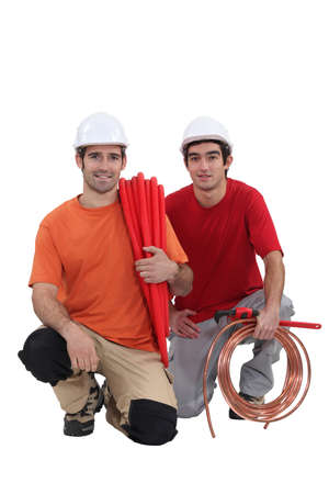 Kneeling tradesmen holding building materials and tools Stock Photo - 16166869