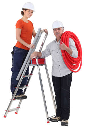 female plumber on ladder with male tutor photo