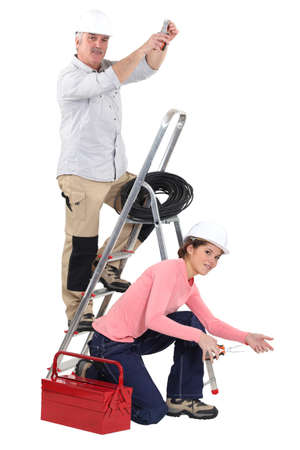 rungs: Electrician and his young female helper Stock Photo