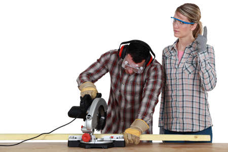 female construction worker: Couple with a circular saw Stock Photo