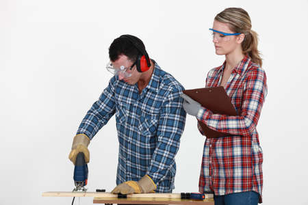 Man using band saw whilst woman supervises photo