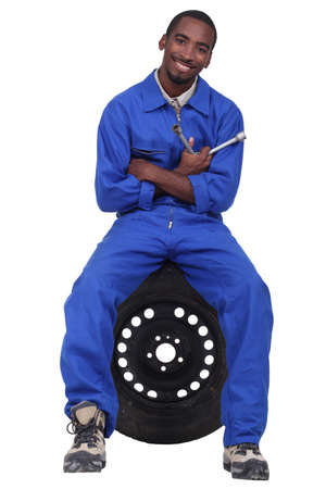 medium body: Mechanic sitting on a wheel Stock Photo