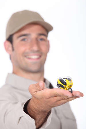 young man presenting a miniature scooter model photo