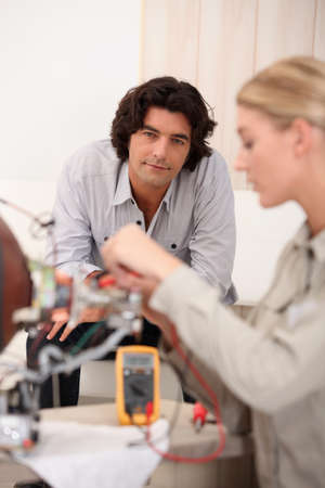 Woman repairing computer and man sitting on a sofa photo