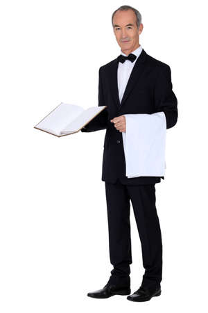Grey haired waiter holding menu and table cloth photo