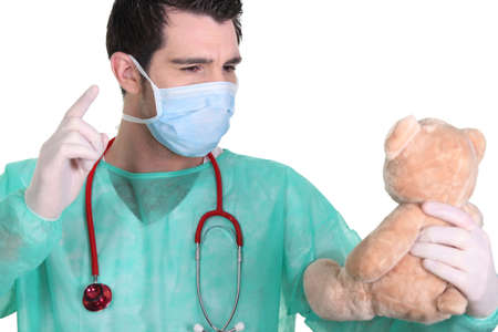 angry teddy: Man dressed as a surgeon quarrelling with teddy bear
