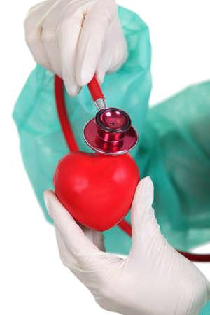 plastic heart: Chirurgo ascolto di un cuore di plastica con uno stetoscopio