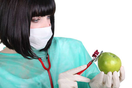 gloves nurse: Female medic checking the pulse of an apple
