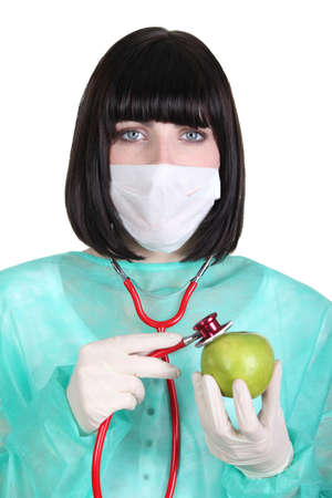 Female surgeon holding a green apple photo