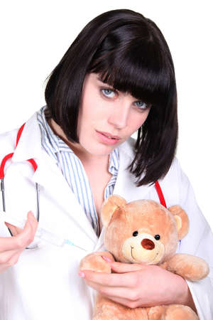 Doctor administering an injection to a teddy bear photo