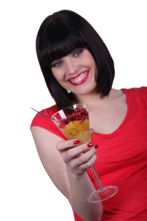 Woman holding a champagne glass full of fruit salad photo