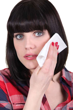 Woman wiping her face with a tissue photo