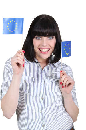 portrait of jovial brunette holding European flags photo