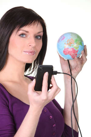 nomad: Woman plugging her cellphone into the world