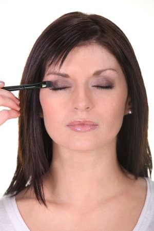 collarbone: Woman applying eyeshadow