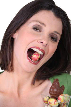 a woman with an Easter egg in the mouth photo