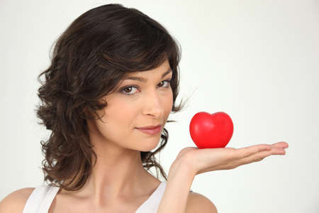 dominate: young woman holding a plastic hearth in her hand