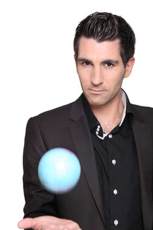 A stylish man playing with a blue ball