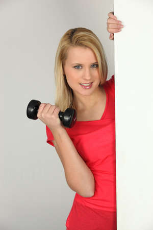 Young woman with a dumbbell photo