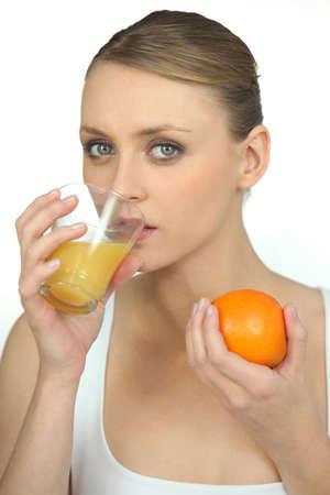 Woman drinking orange juice photo