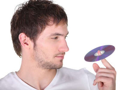 Young man spinning a digital recording disc on his finger photo