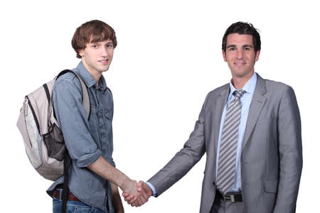 etiquette: Teenager shaking hands with a man in a suit Stock Photo