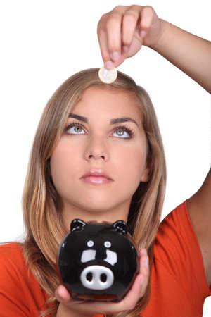 put away: Blond teenage girl with piggy bank