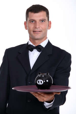 Waiter serving a piggy bank photo