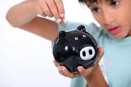 boy putting a coin into a money box photo