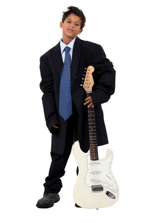 loose fitting: Boy in loose fitting suit stood with electric guitar