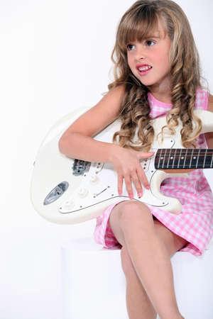petite fille avec robe: petite fille blonde jouant de la guitare électrique Banque d'images