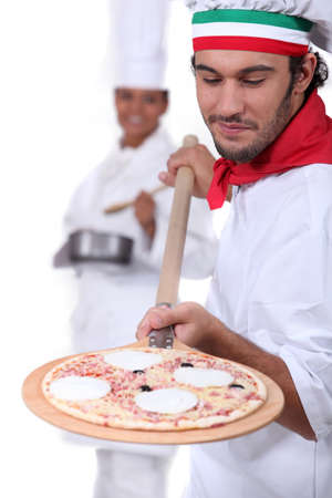Pizza man and female cook in the background photo
