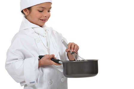 whipping: Young chef mixing a sauce
