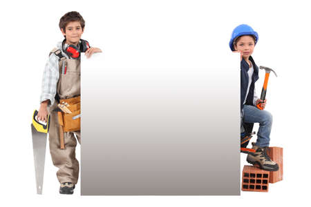 make belief: Children pretending to be construction workers standing around a blank sign