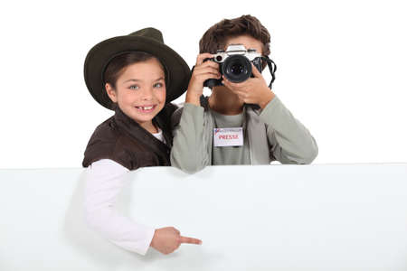 Child press photographers with a board left blank for your message photo