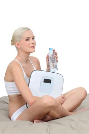 Young woman in her underwear with scales and a bottle of water Stock Photo - 16190450