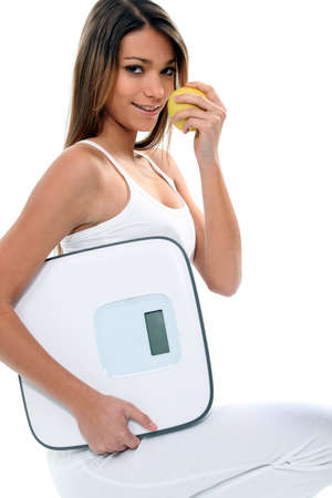 idealism: young and thin woman with an apple and a bathroom scale