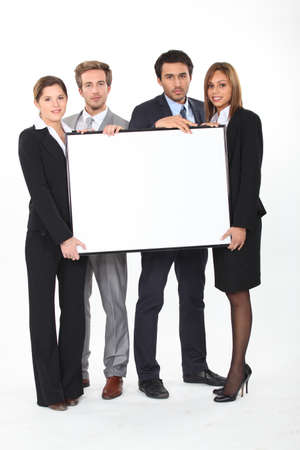 Four young executives holding a framed board left blank for your image photo