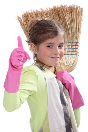 broom handle: Little girl with broom Stock Photo