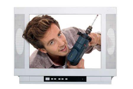 coming out: Man drilling in television set