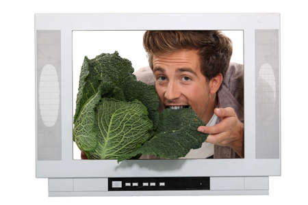 Man eating a cabbage inside a television photo