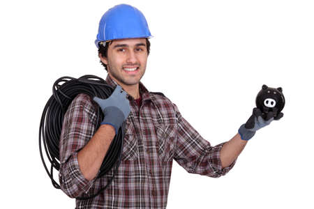 cabling: Tradesman holding electric cabling and a piggy bank