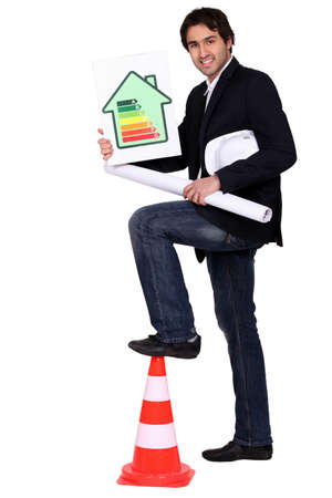 Engineer holding an energy efficiency rating chart and a rolled up drawing Stock Photo - 16190464