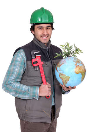 portrait of manual worker holding globe and spanner photo