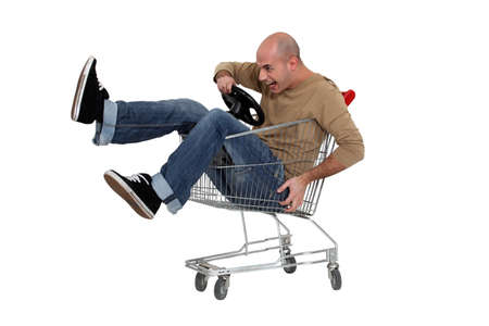 silliness: Man racing a shopping trolley Stock Photo