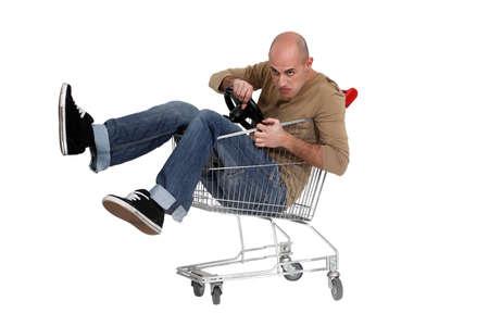 trolly: Man sat in shopping trolley with steering wheel