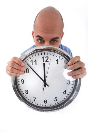 anguished: Bald man carrying a clock, studio shot